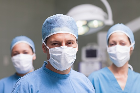 Medical team looking at camera in operating theater